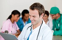 Young male Doctor Smiling at the camera with his team in teh background