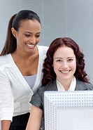 Beautiful businesswomen working together in office with a computer