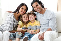 Cheerful family watching TV together sitting on a sofa