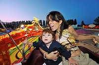 Mother and child on rides and ferris wheel