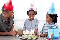 Smiling little girl and her family celebrating her birthday in the kitchen