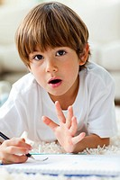 Animated little boy drawing lying on the floor in the living_room