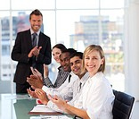 Smiling senior leadership applauding in a meeting