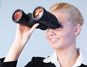 Happy business woman looking outwards thorugh binoculars Focus is on the Person