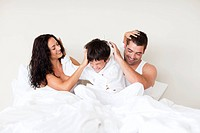 Happy couple and son playing in bed