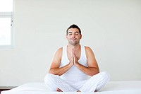 Young man sitting on bed meditating with clossed eyes