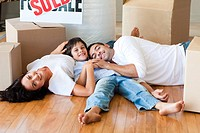Happy family in a new house lying on floor with boxes