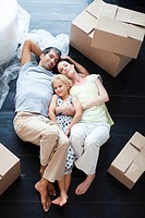 Parents and daughter lying on the floor of their new house