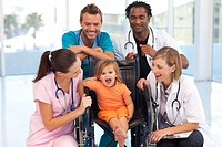 Group of doctors playing with a baby in a wheelchair