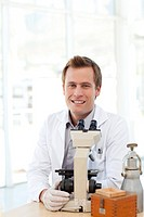 Male scientist looking at a slide under a microscope in a laboratory