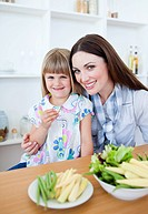 Cheerful little girl eating vegetables with her mother in the kitchen