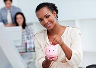Confident businesswoman saving money in a piggy_bank at her desk