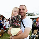 Man holding his young daughter in his arms at the Square Festival, B