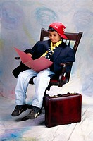 Boy dressed as executive sitting on chair MR158