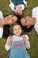 Cute little girl lying in a circle with her family in a park