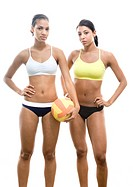 Serious, athletic volleyball players in uniform holding volleyball with hands on hips