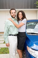Happy couple standing in driveway of home next to car