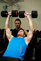 Man lifting weights in gym with man spotting him