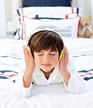 Adorable little boy listening music with headphones on lying on his bed