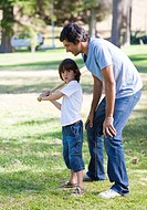 Happy father playing baseball with his son in the park