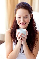 Beautiful woman drinking a cup of coffee in bedroom in the morning