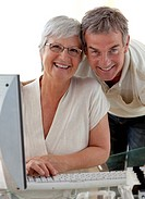 Happy senior couple using a computer at home