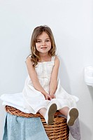 Little girl sitting in bathroom smiling at the camera