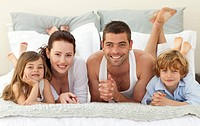 Portrait of happy family lying in bed together