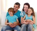 Family in living_room sitting on sofa together watching television