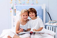 Smiling children reading a book in bedroom