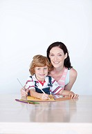 Mother and son drawing with copyspace looking at the camera