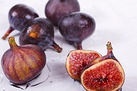 Six Mediterranean figs with one sliced in half  Ficus carica  Foreground focus