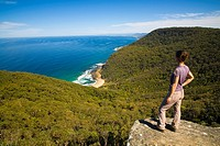 Australia, New South Wales, Royal National Park  Female hiker walking the coastal path takes a break to look down on Werrong Beach from a rocky lookou...