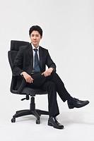 Businessperson sitting on chair, portrait