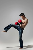 Young bare_chested man wearing boxing gloves