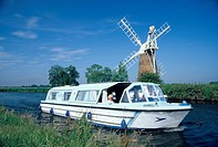 Leisure boats on canal next to How Hill windpump, Norfolk Broads, England