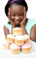 Jolly young woman looking at cakes against a white background
