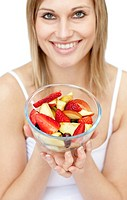 Happy woman holding a fruit salad against a white background