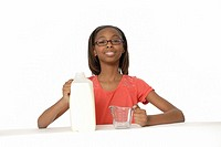 10 year old girl measuring milk in measuring cup