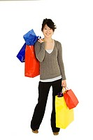 Beautiful Asian teen holding shopping bags while standing on a white background