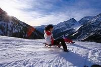 Two persons sledging in the mountains, Staller Sattel, Antholz, South Tyrol, Italy, Europe