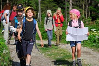 Group of hikers with children, girl reading a map, Bavarian Alps, Upper Bavaria, Bavaria, Germany