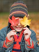 Boy hiding behind autumn leaves