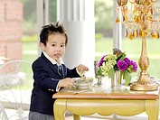 Dressed up young boy eating noodles