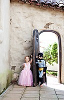 Girl in princess costume and boy in batman costume playing