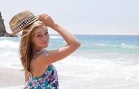 Teenage girl in hat at beach