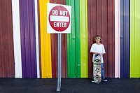 Boy with skateboard in front of colorful striped wall