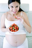 Pregnant woman eating strawberries. She is eight months pregnant.