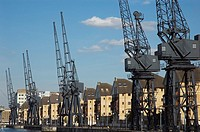 Houses and cranes at Britannia Village next to Royal Victoria Dock, London, England
