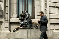 A businessman passing by the copper lion outside the former HSBC Building on the Bund, Shanghai.